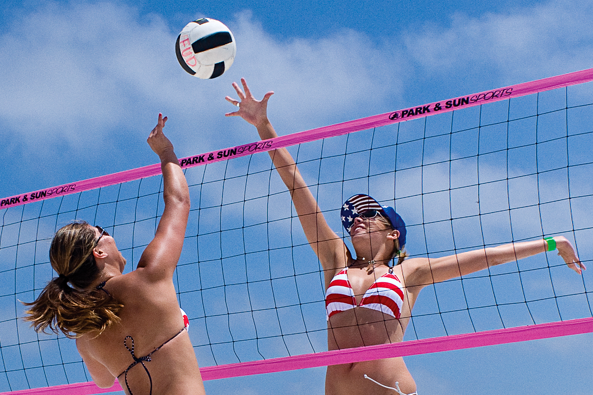 Pink Spectrum 2000 Beach and Grass Volleyball Net System set-up on the beach