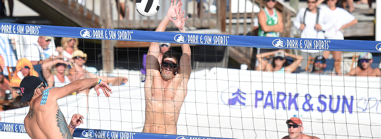 Mens' pro beach volleyball playing above the net